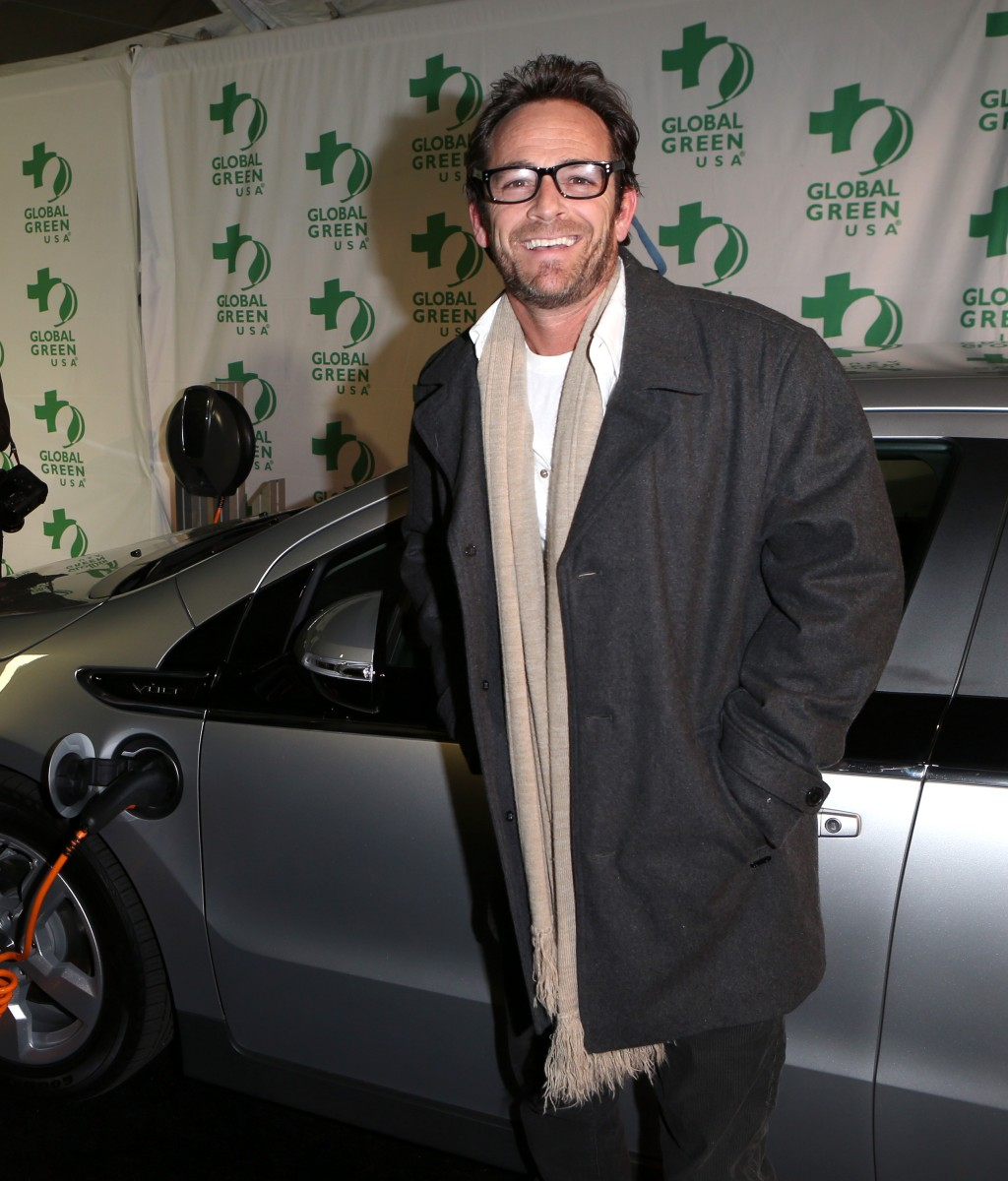 Luke Perry poses with a Chevy Volt at the pre-Oscar event