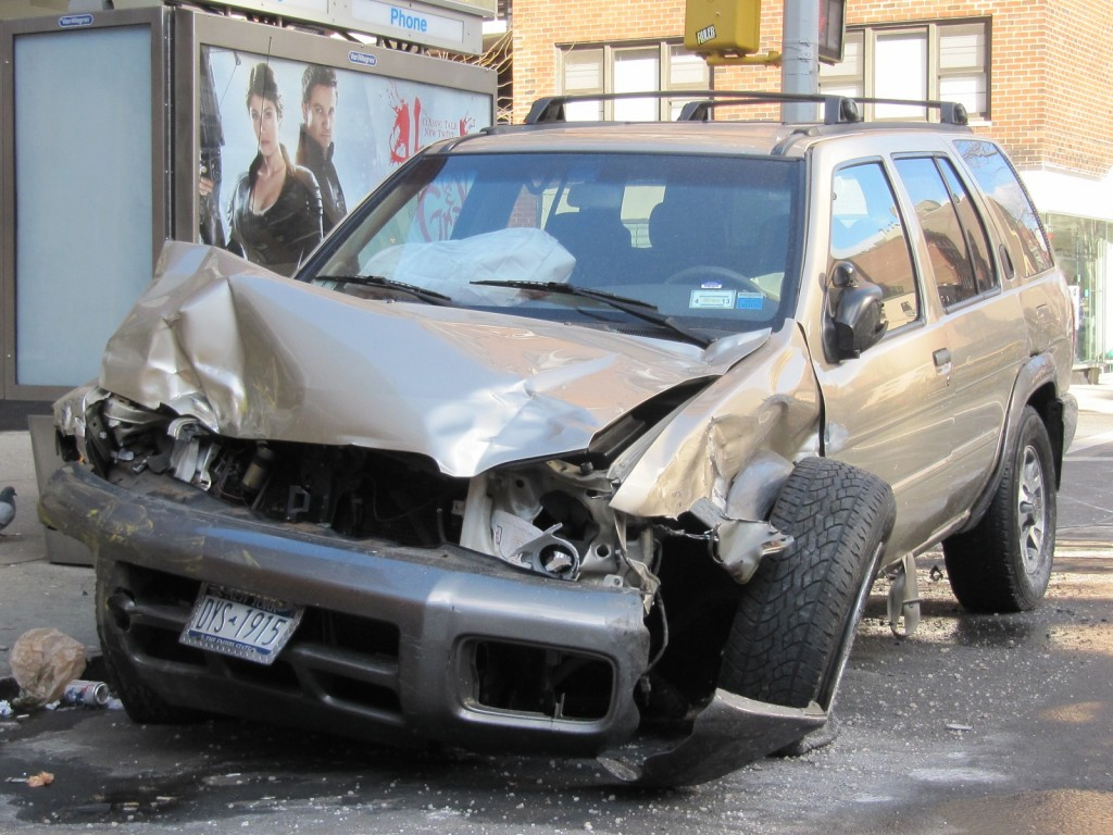 Wrecked Nissan Pathfinder parked at the side of the street in New York City