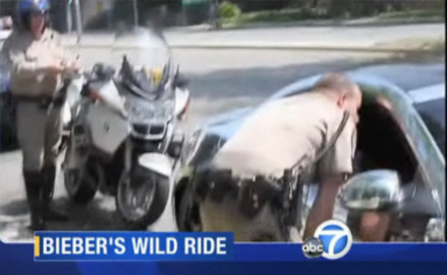 Justin Bieber talking to police in his chrome Fisker Karma - Image courtesy KABC-TV