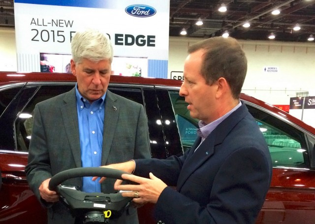 Michigan Governor Rick Snyder with Ford's steering wheel technology at ITS World Congress, Detroit