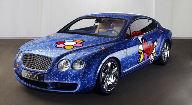 The car's paintwork is adorned with a large, happy flower, little stars, squiggles and psychedelic signs
