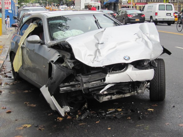 Wrecked BMW 3-Series parked at the side of the street in New York City