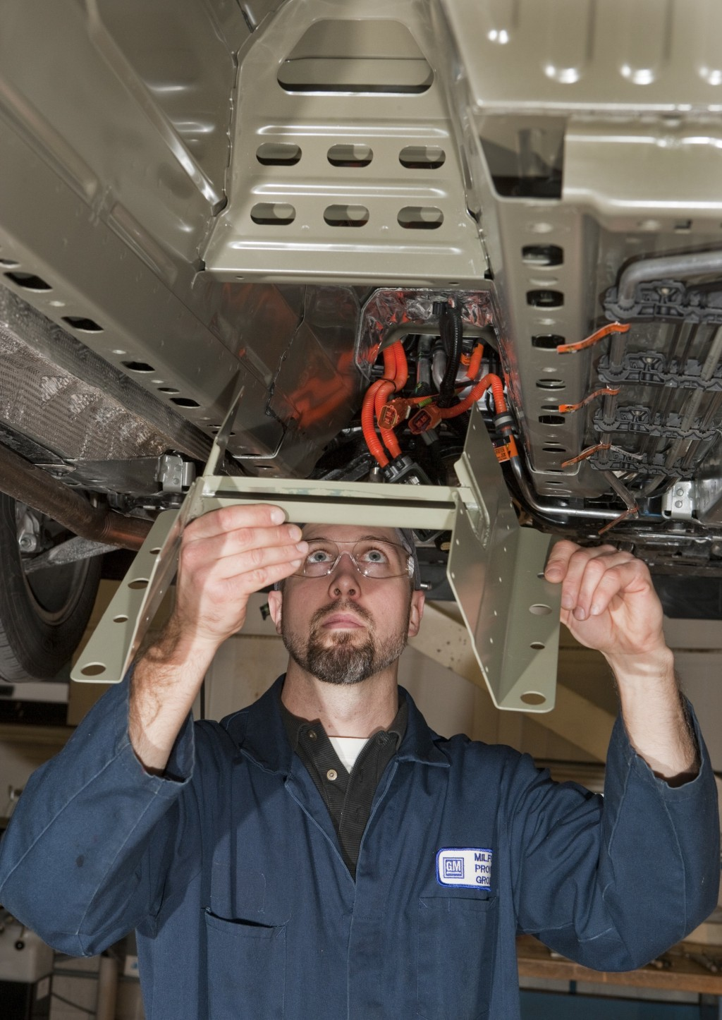 GM engineer fits structural reinforcement to distribute crash energy away from Chevy Volt battery.