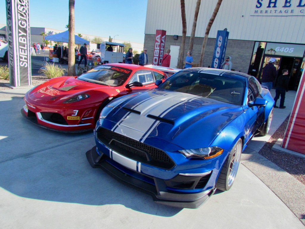 A Ferrari racing car and a Shelby Super Snake Ford Mustang were parked in front of the Shelby Herita