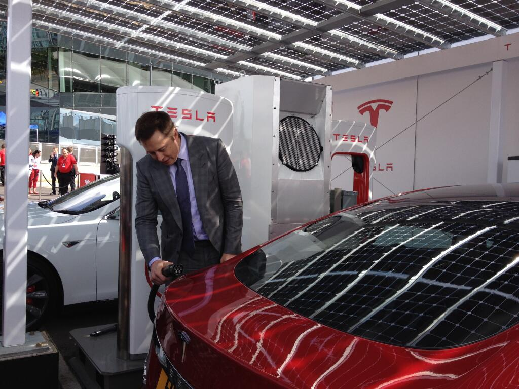 Elon Musk plugs a Tesla Model S into a Supercharger (Image: deanslavnich on Twitter)