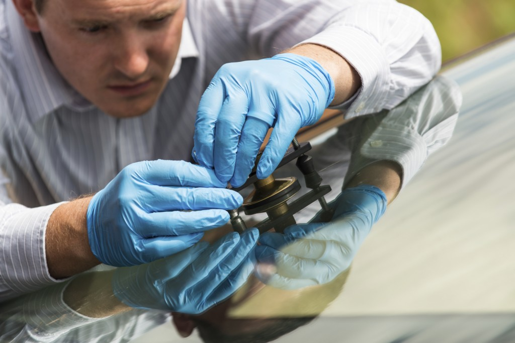 Glass repair -- mechanic works on cracked windshield