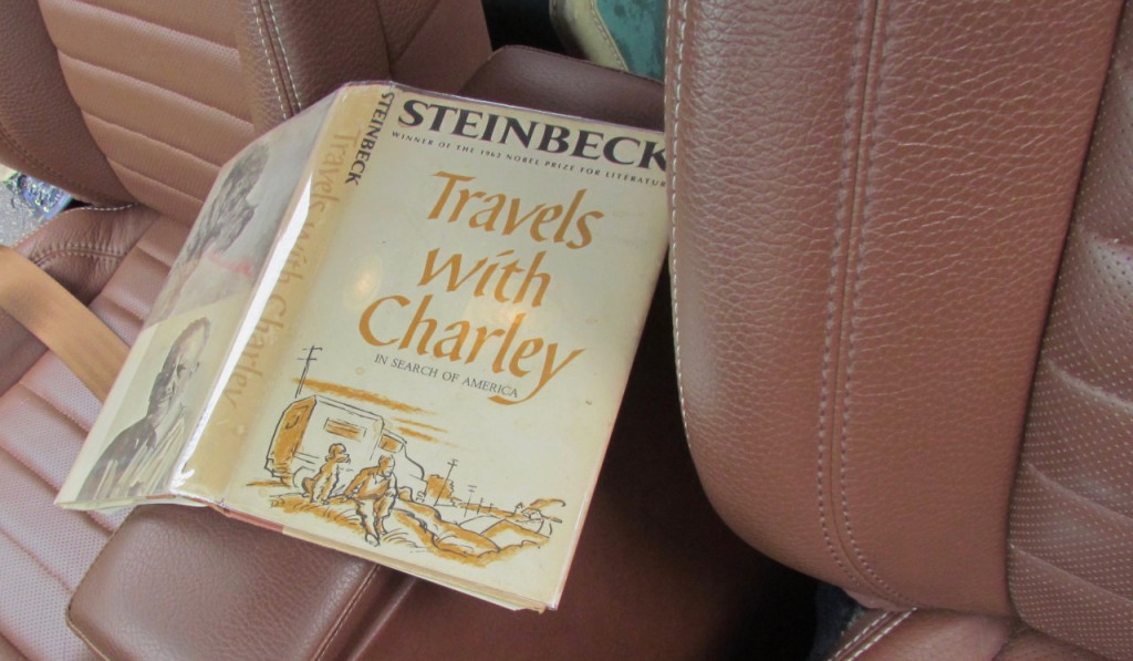 An early edition of 'Travels with Charley' on the front seat of a car makes for a nice period-correct touch