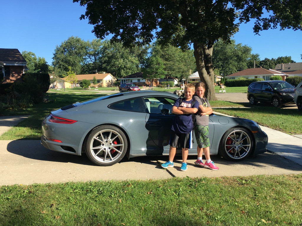 The kids pose before the 2017 Porsche 911 Carrera