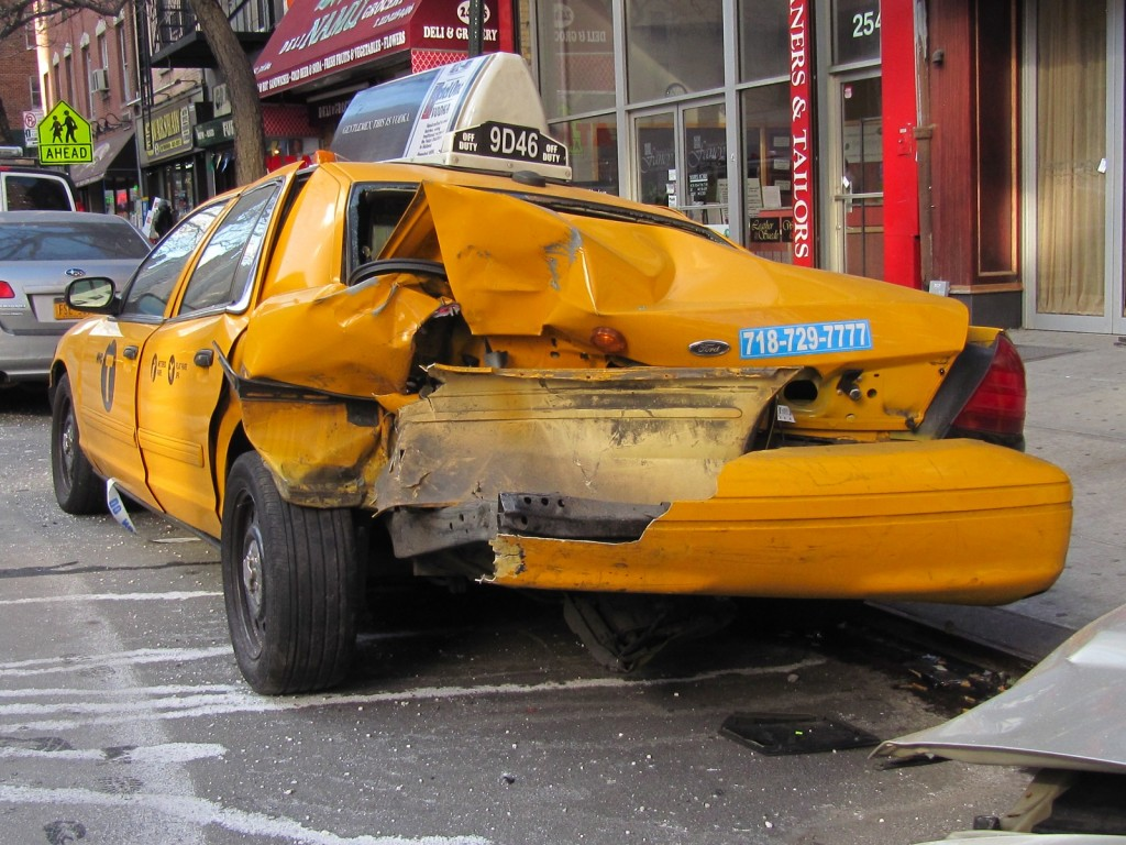 Wrecked Ford Crown Victoria NYC taxi cab parked at the side of the street in New York City
