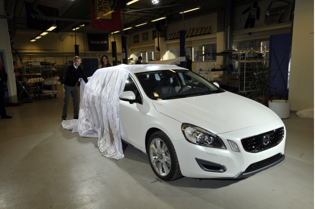 Journalists look over the 2011 Volvo V60 PHEV in final preparations before the 2011 Geneva Motor Show