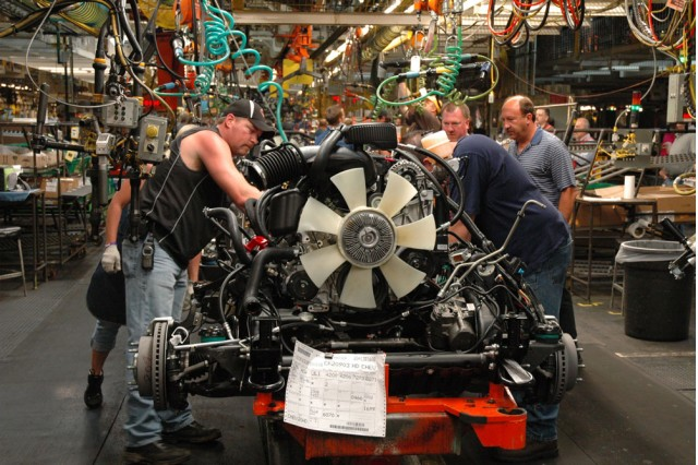 Auto workers adjusting the chassis of the 2011 Chevrolet Silverado HD