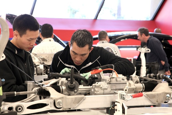 Tesla Model S workshop - technicians assembling a front sub-frame