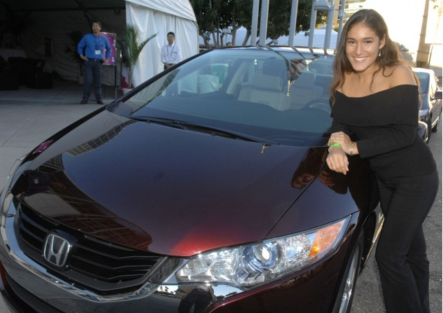 Actress Q'orianka Kilcher poses next to a Honda FCX Clarity at the 2007 Los Angeles Auto Show.