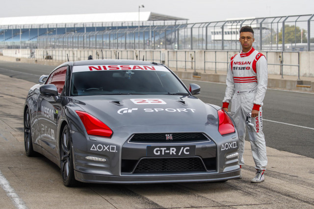 Jann Mardenborough drives a Nissan GT-R around a racetrack with a video game control
