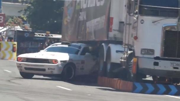 Samuel Hübinette drifts his Dodge Challenger under a semi truck