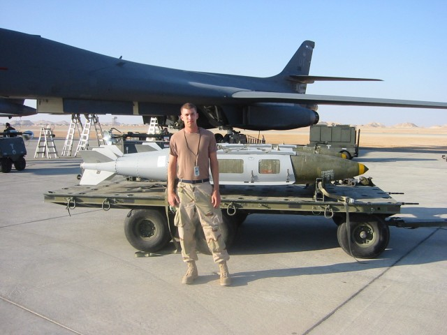 U.S. Air Force avionics technician Tim Goodrich in Oman, with plane flown over Afghanistan